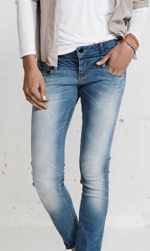 Badia Jeans. Smarte jeans fra danske Plus Fine. Modellen har almindelig taljehøjde, men er syet med dobbelt linning og syner derfor mere lavtaljet. Har to lommer fortil og to påsyede baglommer. Detajeret med mærkeblåt bånd i taljen. Jeansene er i en lys vask med forvaskning. Materialet er 100% bomuld.