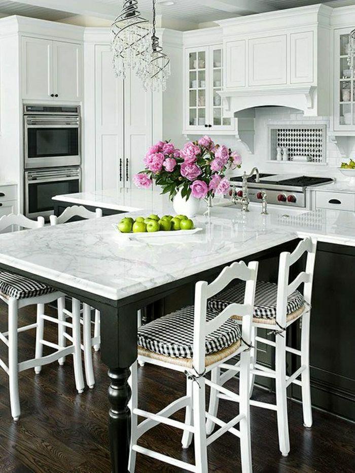 table de cuisine en marbre blanc, fleurs sur la table, meubles blancs en bois