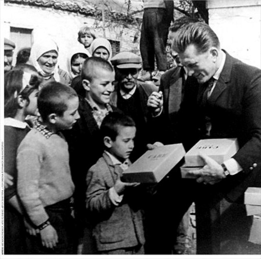 Greece, 1947(?). Actor Kirk Douglas is distributing boxes with school items in…