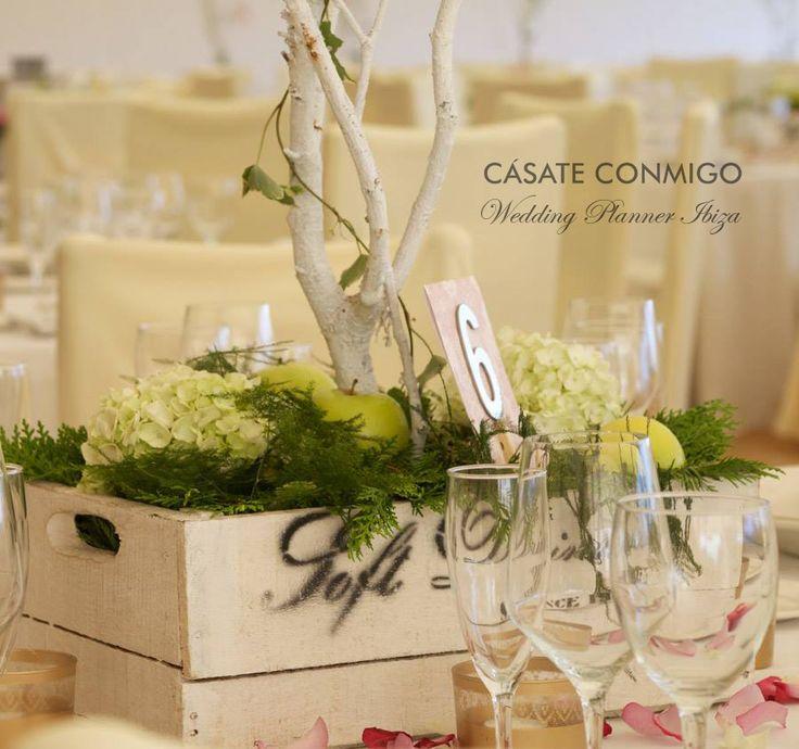 Centro de mesa rústico con caja de fruta, musgo, hortensias, manzanas verdes y troncos altos.