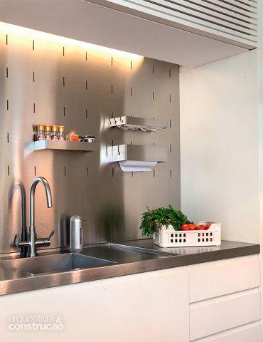A cozinha (Pica-Pau Marcenaria) traz painel de aço inox Smart Kit (Mekal). Os rasgos permitem encaixar suportes que organizam itens pequenos. Projeto Vanessa Martins Miranda.