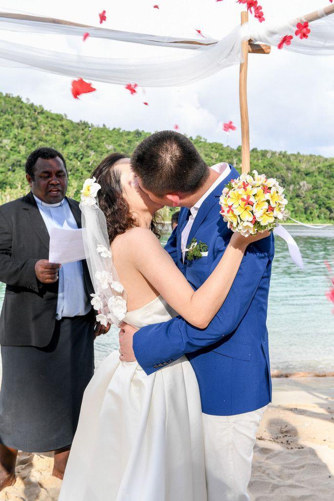 Bride and groom kissing under rose petals Paradise Cove Island Resort, Yasawa, Fiji. Photographed by Anais Photography.