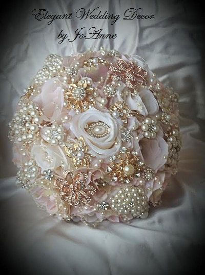 ELEGANT 27 in Diameter CUSTOM BLUSH PINK & IVORY ROSE GOLD BOUQUET - $499.00 - DEPOSIT $299.00 WHEN YOU PLACE YOUR ORDER - BALANCE $200.00 DUE WHEN YOUR ORDER IS 100% COMPLETED This is a Vintage Inspired Brides Jeweled Bouquet in Ivory champagne and soft Blush Pink flowers, This bouquet is elegantly accented with all rose gold and gold brooches and gems. The handle is of ivory satin with a beautiful rose gold large gem in the handle center. The flowers have an added touch of lace in ivory…