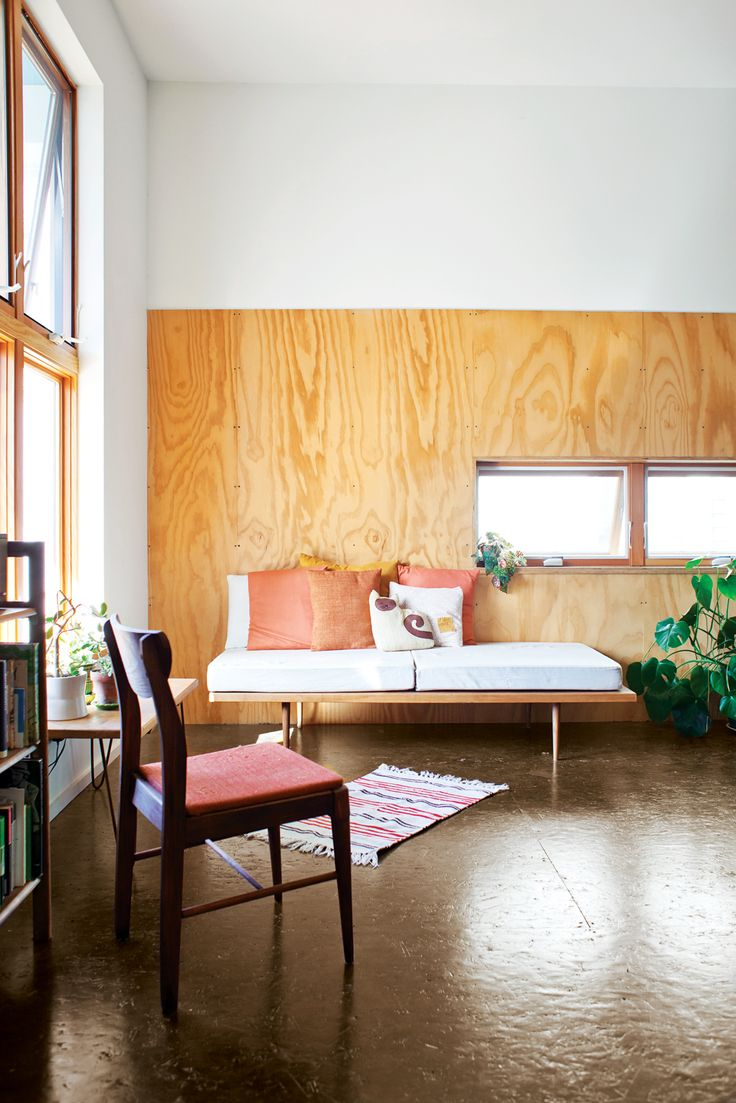 In the living room of a Knoxville house, a bench offers a cozy spot to sit.Ply paneling - Dwell