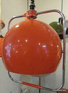 Fraaie goed uitziende hanglamp van Gepo met grote oranje bol in een vierkant chroom omlijsting. Aan een pendule koord en metalen plafond kapje. De bol kan draaien desgewenst. Er zit een oude oranje gl