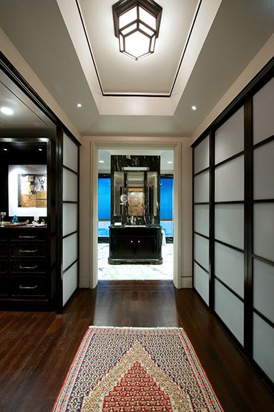 A timber floored Walk in Wardrobe leads to the a His Bathroom at Apartment DNNW, Mumbai - Architecture BRIO, Mumbai / India