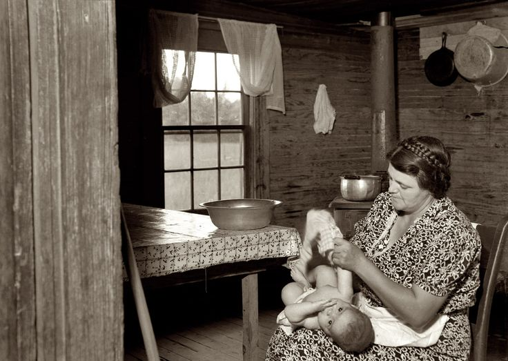 July 1939. Whitfield family. Wife of tobacco sharecropper drying the baby after its bath in the kitchen. Person County, North Carolina, near Gordonton. Medium-format nitrate negative by Dorothea Lange