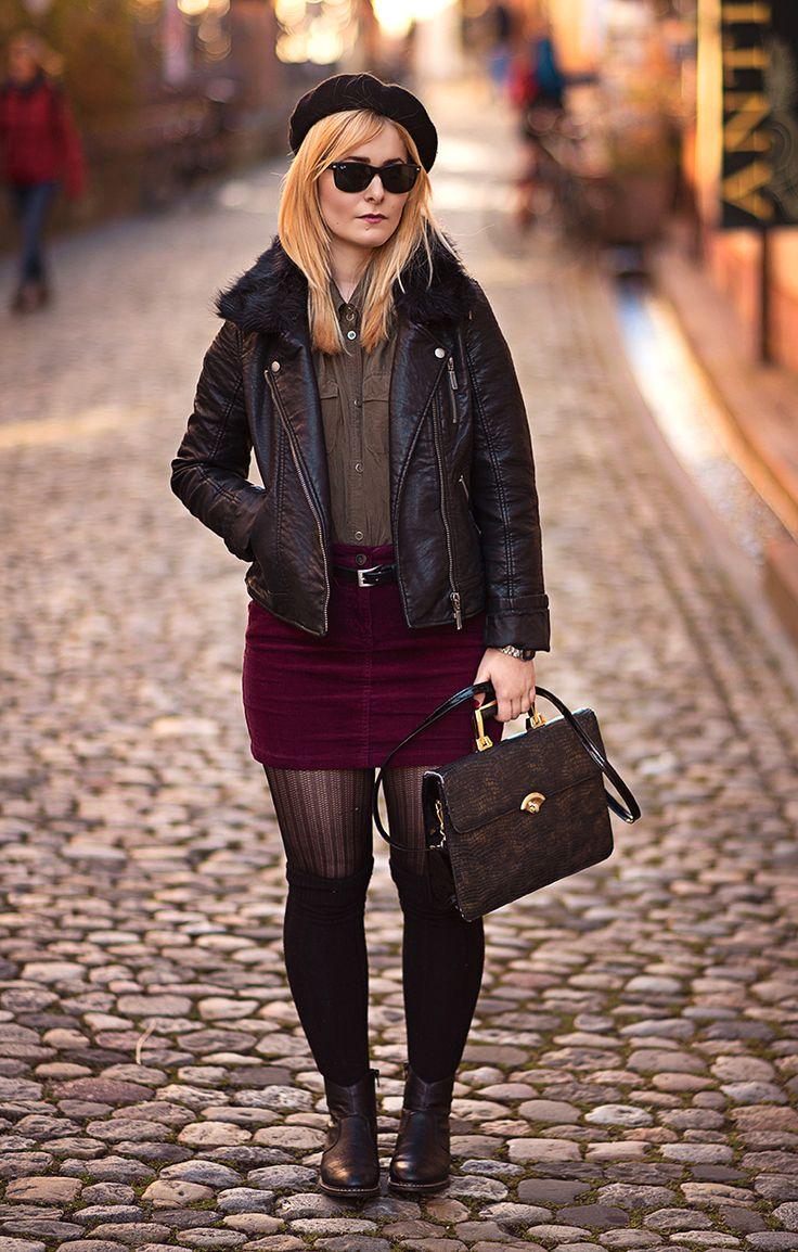 Christina Key trägt eine schwarze Lederjacke kombiniert mit einem weinroten Kord Rock und schwarzen Knie Strümpfen
