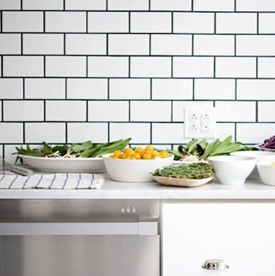 11 Backsplashes for a Unique Kitchen: Like black tie for the kitchen, white subway tile with black grout never goes out of style. And although it looks sophisticated, the material costs are low, making this stylish look quite affordable.