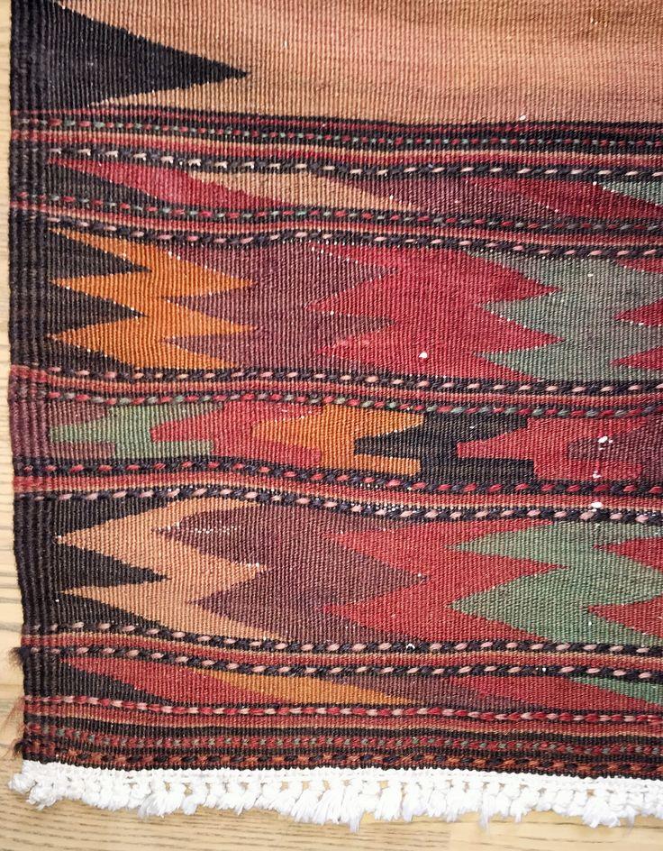 Denne Soufreh er en gyldenbrun kelim (fladvævet) med et sort zigzagmotiv på hver langside og for enderne forskellige mønstre i brune, sorte, blå, og røde nuancer samt med broderede striber. Tæppet er vævet af kurdiske stammer i Iran af kameluld på en bomuldstrend. Vintage: 60-80 år Størrelse: 185*90 cm