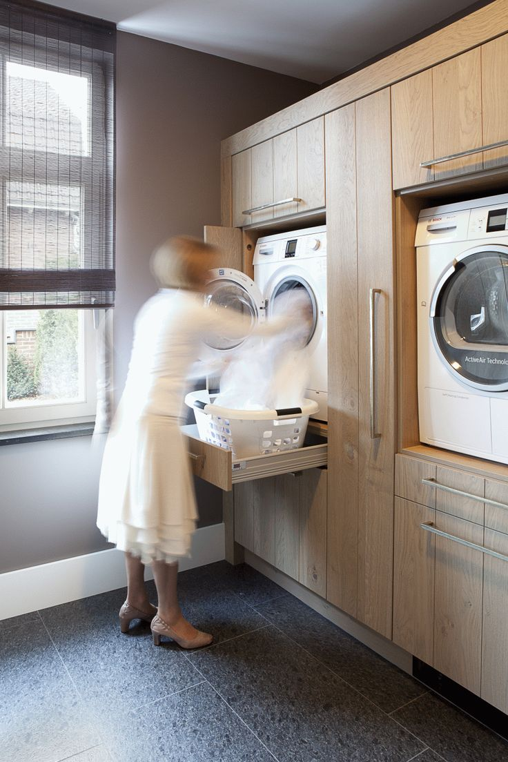 Raised washer and dryer with drawers below to hold a laundry basket. So smart - a functional and ergonomic solution that could work for modern or traditional styles