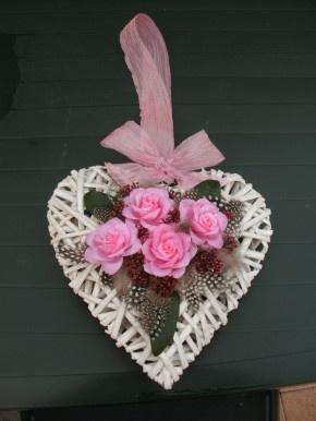 rotan hart, zelfgemaakte bloemetjes uit koffiefilters, gedoopt in gesmolten kaarsvet. Daarna versierd met veertjes, blaadjes en lint om op te hangen