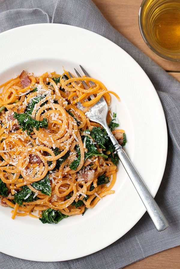"In this healthy spaghetti carbonara recipe, ""spiralized"" sweet potato noodles (similar to zoodles) take the place of traditional pasta. Kale is added for fiber, flavor and crunch, but any dark leafy green, such as spinach, chard or collards, would also be a nice addition."