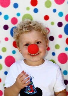 Clown noses and a colorful backdrop create the perfect photo booth for a Carnival Birthday Party!!
