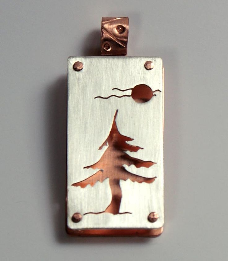 tree and moon/ sun cut in top layer of metal on metal by  Julie Sanford