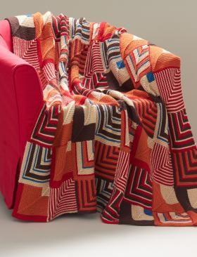Яркое одеяло с геометрическим узором связано из квадратных мотивов, каждый из…