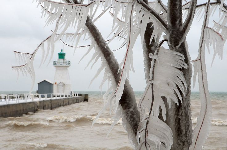 Icicles hang from trees next to the lighthouse and pier on Lake Erie, in Port Dover, Ontario, Canada on Friday, Jan. 13, 2012. (AP Photo/The Canadian Press, Dave Chidley)