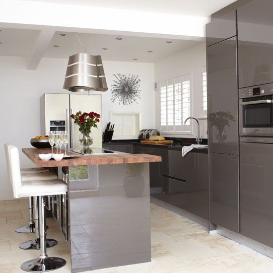 This kitchen has soften the grey with a wooden worktop and incorporated a highly fashionable gloss finish as well.