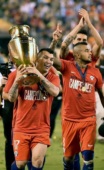 #COPA2016 #COPA100 Chile's Gary Medel holds the Copa America Centenario trophy after winning the final by defeating Argentina in the penalty shootout next to Arturo...