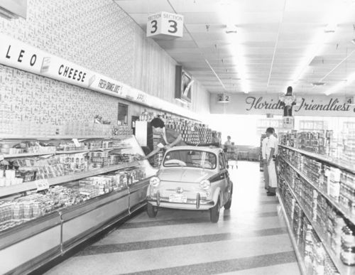 Groceries weren't always displayed on such orderly, open-access shelving. Before expansive supermarkets with wide aisles became common, goods were located behind a counter and retrieved by a store clerk upon request. The grocery shopping popular today has a name: self-service. Publix Supermarkets showcased their wide aisles and a self-service dairy case by driving a shopper around a new store in a tiny car, circa 1957.