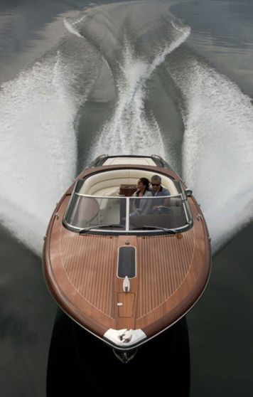 Chris Craft wooden boat with dynamic wake patterns behind it, glassy water in front and clouds above reflected in the glossy laquered hull... beauty.