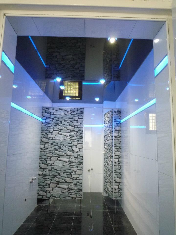 Baño minimalista con iluminación perimetral Led y techo lacado negro