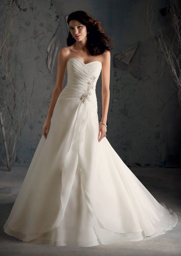 Draped and alive, this satin organza wedding dress is Mori Lee Blu 5169 with it stunning crystal beading along the left side of the midriff where all the draping begins. The floor length wedding gown is amazing with a strapless neckline and a corset laced up the back bodice for that alluring romantic look from your fairytale dreams. #timelesstreasure