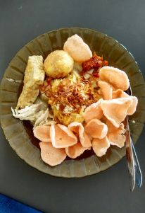 Lontong Capgomeh is one of Peranakans' Specialties. It comes as a dish-meal (food served in a dish to be eaten at one time). Included in each portion is some pieces of rice cake; thin sliced chayote, a fried boiled egg, a piece of fried tofu, all of these three ingredients are cooked in savory coconut milk gravy; shredded chicken breast which is also cooked in coconut milk gravy (opor ayam suwir); spicy chicken liver fritters (sambal goreng ati ayam); and crackers as a delicacy adder.