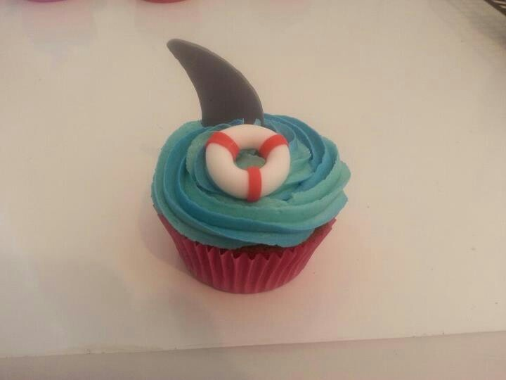 Shark fins and floaties beach themed cupcakes.