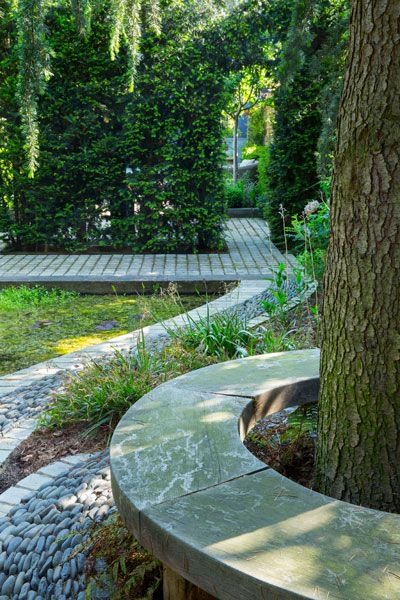 Circular seat around tree, pebble paving by pond, arch in clipped yew hedge