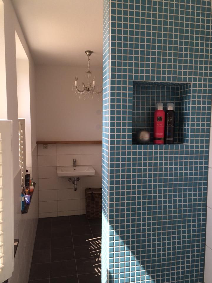 De badkamer in een nieuwbouwwoning werd standaard opgeleverd. Iamm heeft de finishing touch aangebracht met een eiken apothekerskast en een muurtje met mozaïek tegels als afscheiding voor de douche.