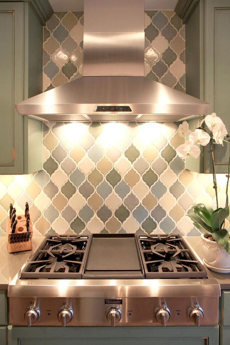 Hand-glazed arabesque tiles form an artful backdrop behind the sleek stainless steel range hood in this neutral transitional kitchen. The diamond pattern adds texture and interest to the cooking area.