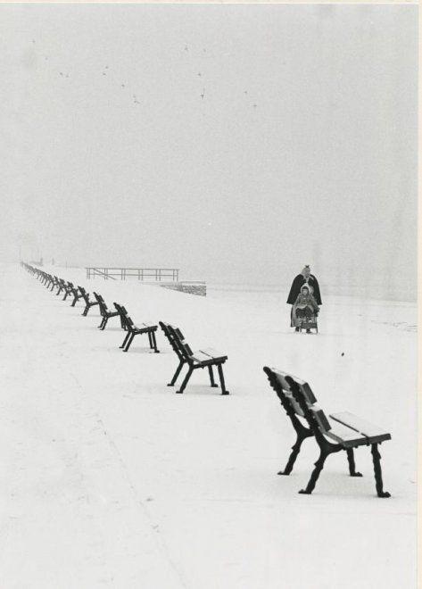 Boulevard in de sneeuw, een vrouw in Scheveningse dracht duwt een slee. ca 1956…