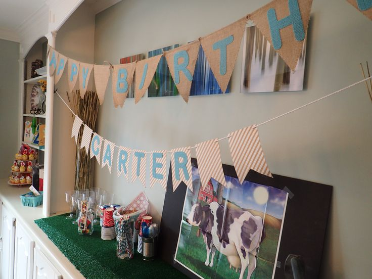 Farm themed birthday decorations including fake grass bought at Home Depot, Pin the Tail on the Cow, cleaned tin cans filled with straws, and a homemade birthday banner.