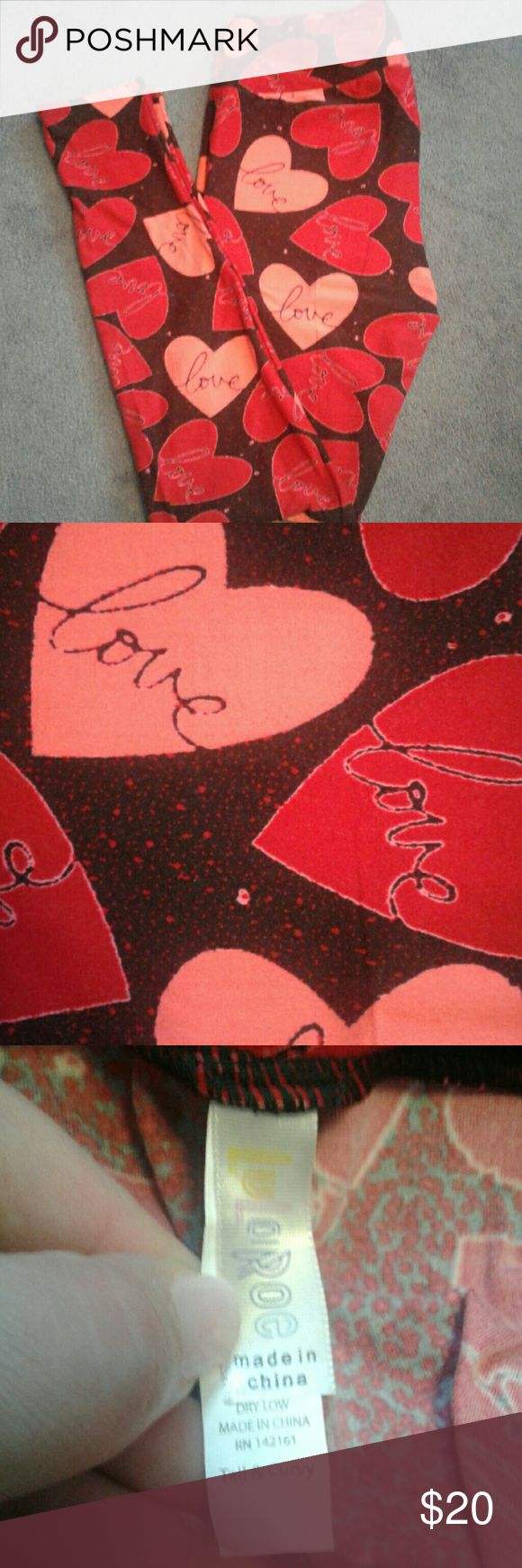 """LulaRoe Valentine's Day leggings Like new, LulaRoe leggings worn once, washed per LLR instructions. Black background with red and pink hearts and the word """"love"""" on them. There is also a pink and red """"splatter"""" pattern on the background. LuLaRoe Pants Leggings"""