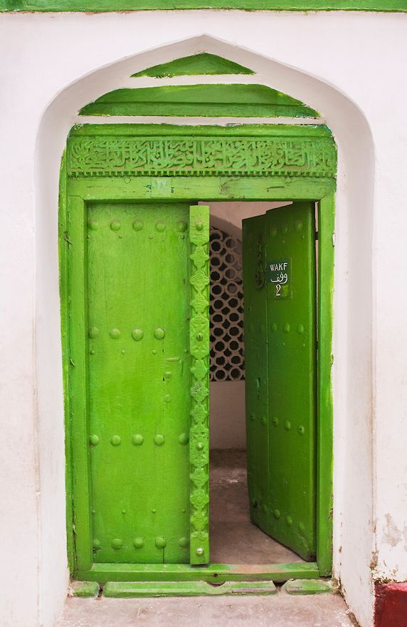 Old rustic historic green doorway with carvings typical of the omani era  in Stone Town, Zanzibar, Tanzania, East Africa.