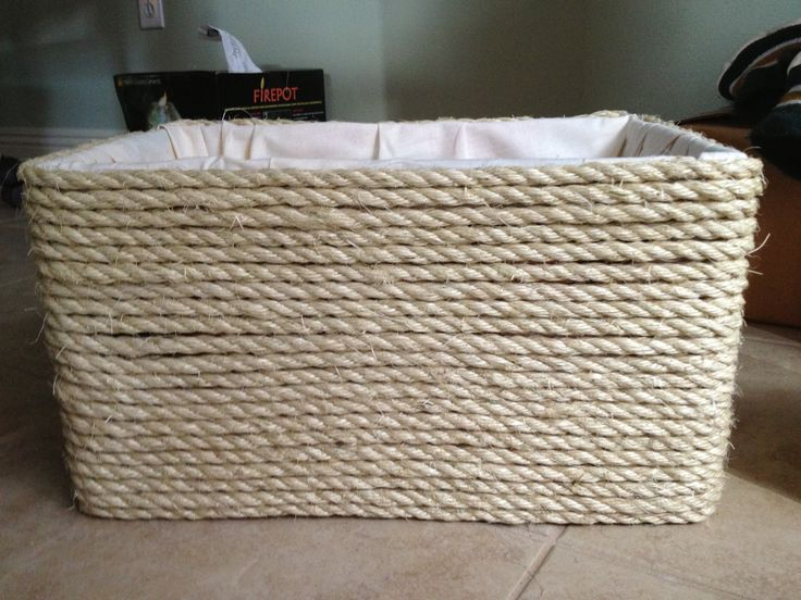 Hate throwing away sturdy cardboard boxes? Line with fabric, glue on rope, and you have a lovely storage option.