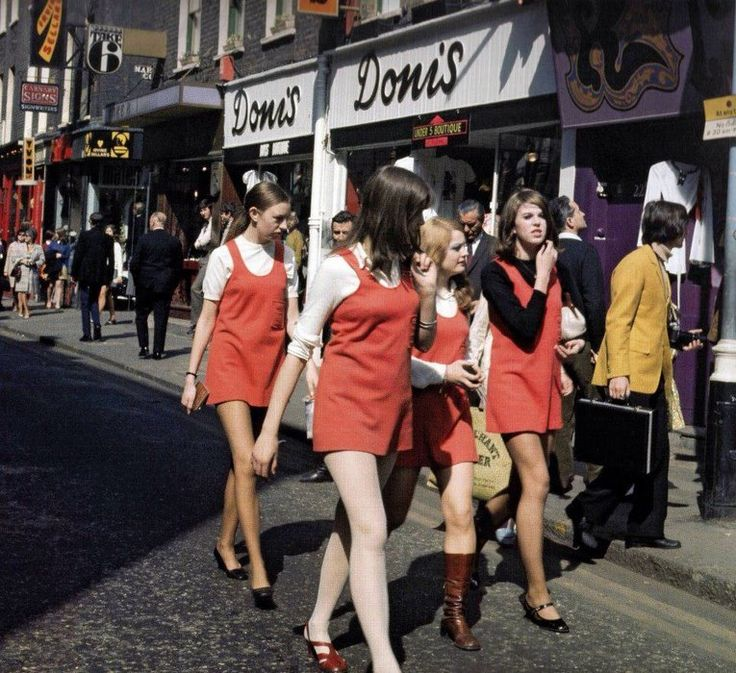 Dolly birds walking through Carnaby Street. You can see the purple Kleptomania boutique in the corner.
