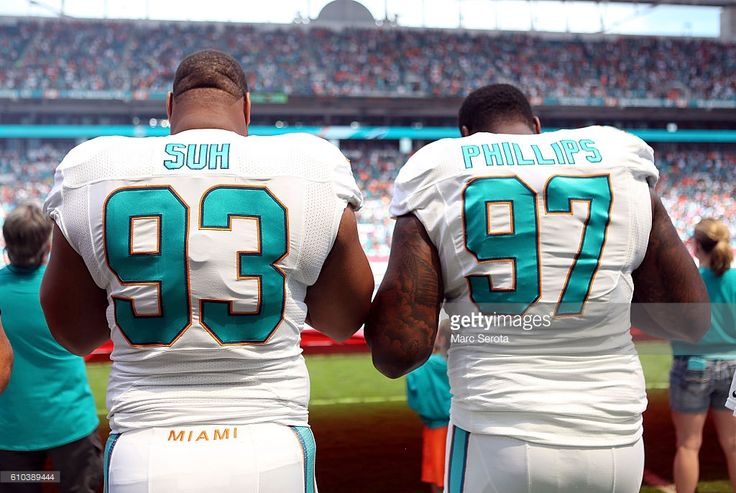 Ndamukong Suh #93 and Jordan Phillups #97 of the Miami Dolphins stand for a moment of silences for Miami Marlins Pitcher Jose Fernandez prior to a game aagainst the Cleveland Browns on September 25, 2016 in Miami Gardens, Florida. Fernandez was killed in a boating accident early this morning.