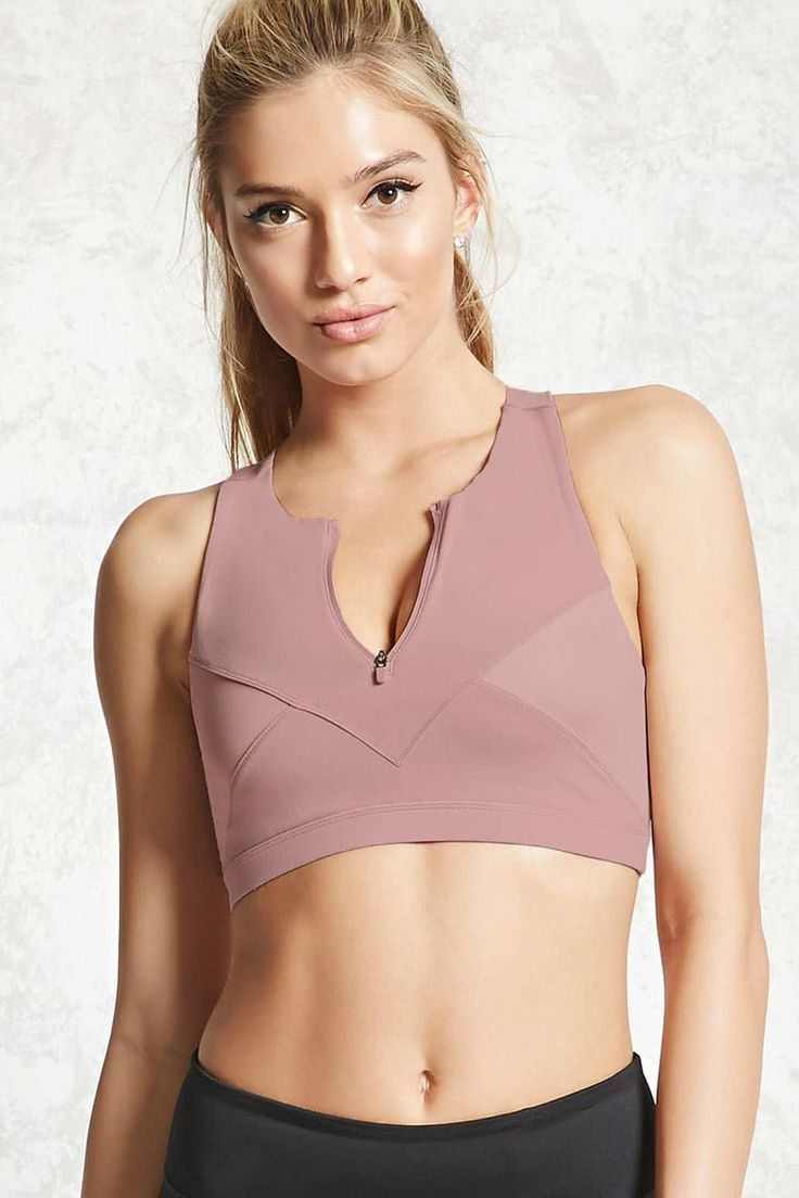 A stretch knit high impact sports bra featuring a zip-up front, removable cups, …