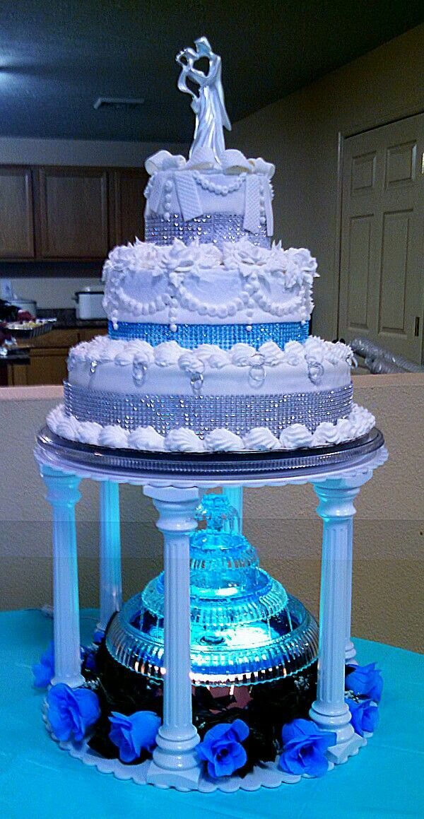 Three tiered silver and teal, aqua blue wedding cake with lighted fountain