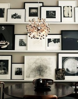 Eclectic assortment of framed black and white photographs on picture shelves.