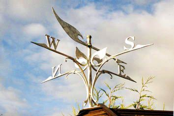 A contemporary wrought iron weather vane whose sculptural forged steel shapes were inspired by the flowing movement of air. It has a galvani...