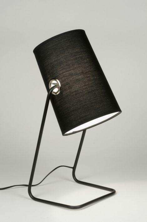 Artikel 88901 Moderne tafellamp in een opvallende vormgeving. Dit armatuur bestaat uit een mat zwart frame met daaraan een zwarte stoffen kap. De binnenzijde van de kap is wit zodat het licht optimaal gereflecteerd wordt. De kap is enigszins verstelbaar zodat u de lichtbundel kunt richten. Een opvallend exemplaar dat ondanks zijn strakke vormgeving toch bijzonder sfeervol is. http://www.rietveldlicht.nl/artikel/tafellamp-88901-modern-metaal-staal_-_rvs-stof-zwart-mat-rond