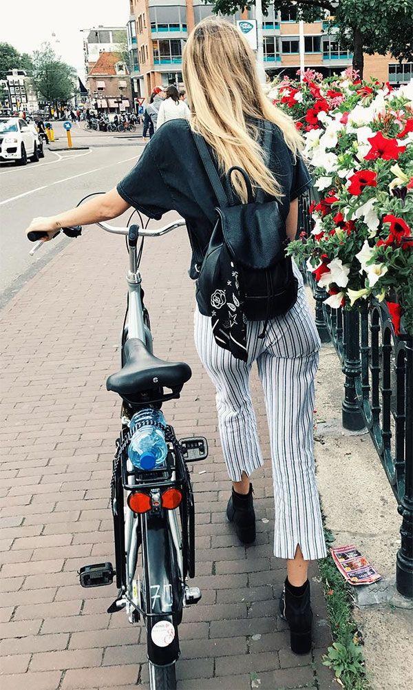 Street style look de Shannon Taylor com calça listrada, t-shirt preta, mochila e ankle boot.