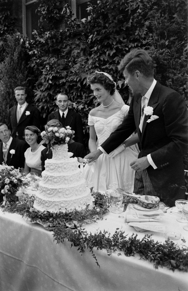 These Rare Photos From JFK And Jackie O.'s Wedding Were Found In A Darkroom  Future US President John F Kennedy (1917 - 1963) and Jacqueline Kennedy (1929 - 1994) (in a Battenburg wedding dress) hold hands as they cut the cake at their wedding reception, Newport, Rhode Island, September 12, 1953. (Photo by Lisa Larsen/Time & Life Pictures/Getty Images)