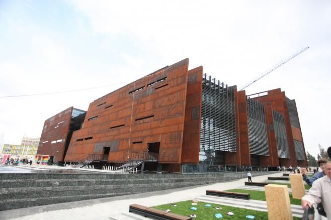 Europejskie Centrum Solidarności Randomised windows and extent of weathered steel cladding comparable to PHSC