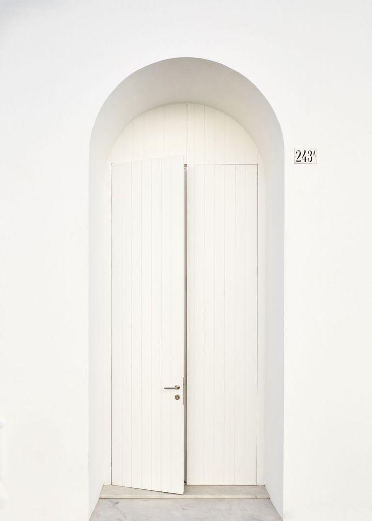 White door under arch. Belém Clube by José Adrião Arquitetos. © Hugo Santos Silva.