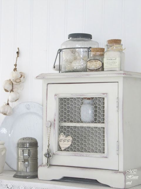 Love the jar with metal carrier on little white cabinet.