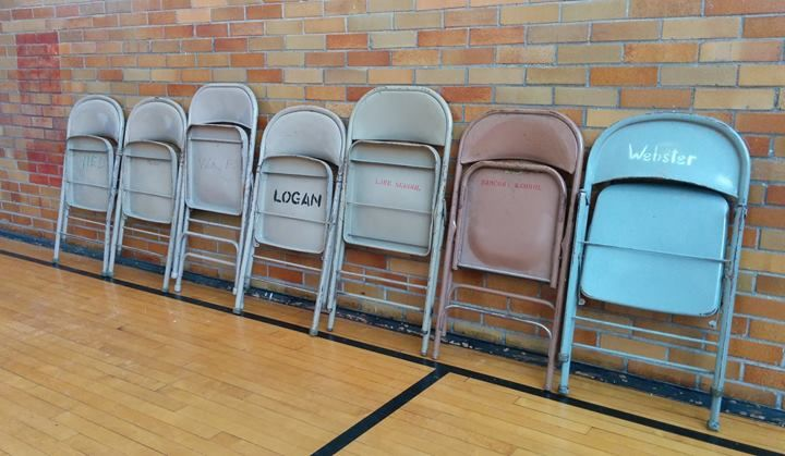 All of the steel folding chairs in this picture were originally located at Granite City schools of yesteryear. Each chair has an original location printed on it.  Left to right: Niedringhaus, Marshall, Washington, Logan, Lake, Nameoki, and Webster. These chairs belong to Granite City School District #9 and were located in the gymnasium at Niedringhaus School, our temporary main library. #sixmilesoflocalhistory